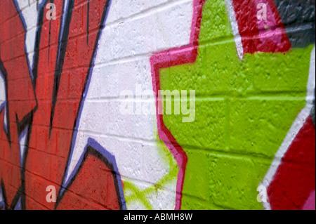 Graffiti sprayed on a brick wall side perspective - Stock Photo