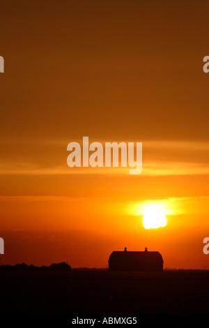Setting sun lighting up clouds behind barn in scenic Saskatchewan Canada - Stock Photo