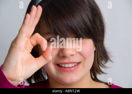 Young 11 year old girl giving the OK sign - Stock Photo
