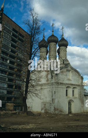 The stark contrast of old and new Assumption Church beside a Communist style apartment block Nizhny Novgorod Russia - Stock Photo