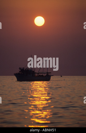 Full moon shines over a night time fishing boat Croatia - Stock Photo