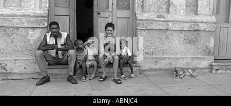 Cuban family seated outside their home Cubans are friendly and welcoming people Cardenas or possibly Havana Cuba - Stock Photo
