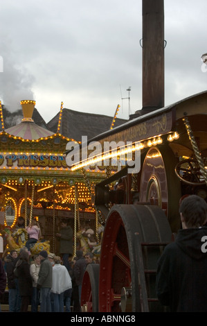Showman's traction engine and galloping horses ride at a Christmas Victorian street fair in Worcester UK - Stock Photo