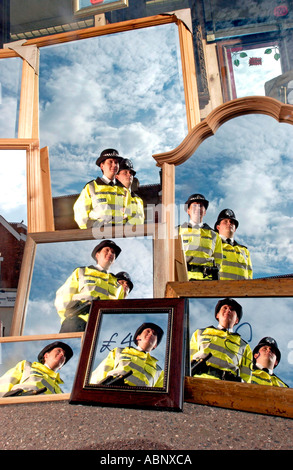 Two police officers, a man and a woman,  reflected in mirrors in shop window in Sussex - Stock Photo