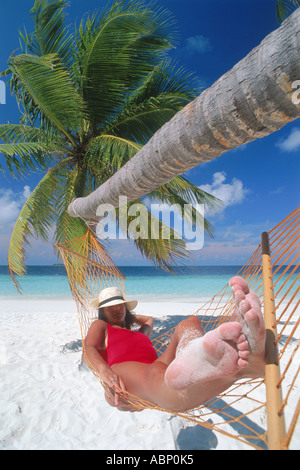 Woman in hat and red bathing suit sleeping in hammock with sandy feet - Stock Photo