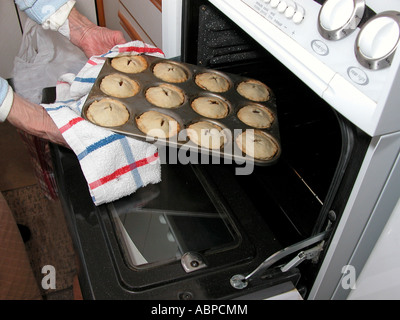 elderly woman taking cooked pastry pies out of the oven in kitchen - Stock Photo
