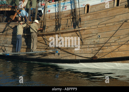 Workmen cleaning and re- caulking wooden hull of sailing ship - Stock Photo