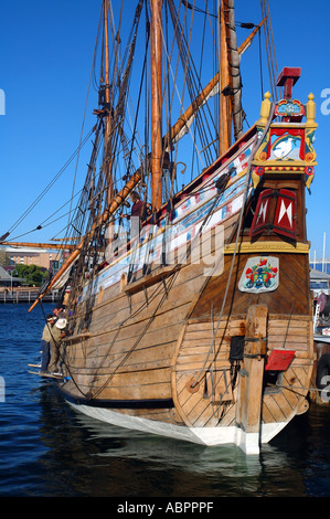 Workmen cleaning and re-caulking wooden hull of sailing ship - Stock Photo