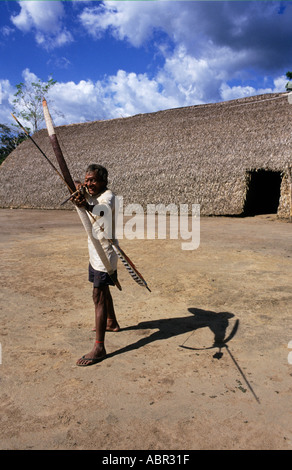 Koatinemo village, Brazil. Assurini Indian man demonstrating his bow and arrow skills outside the House of the Dead. - Stock Photo