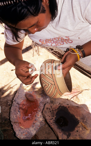 Koatinemo village, Brazil. Assurini Indian woman, Maye, decorating a pot with thin wooden split and ground rock - Stock Photo