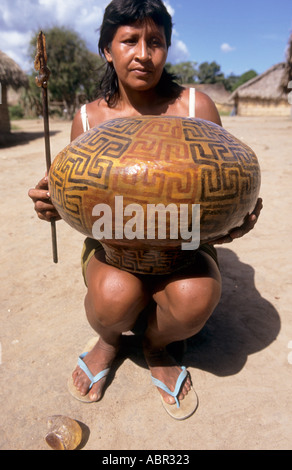 Koatinemo village, Brazil. Assurini woman holding a pot decorated with typical geometric design and stick with resin - Stock Photo