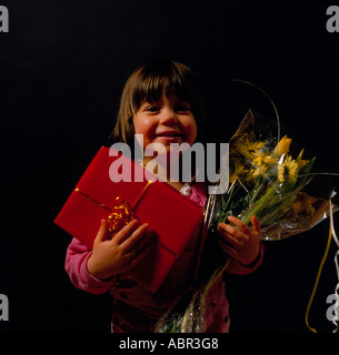 little girl looking at camera with a parcel and flowers.  Photo by Willy Matheisl - Stock Photo