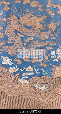 CHINA Detail of a sumptuous dragon robe brocaded with golden threads and silk on an indigo ground Silk tapestry - Stock Photo