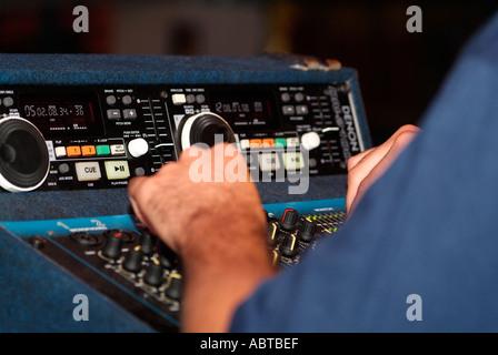 DJ Using an Electronic Mixing Desk - Stock Photo
