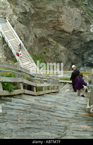 Couple Descend Steep Flight of Steps at Tintagel Castle Cornwall England United Kingdom UK - Stock Photo