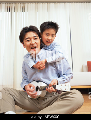A man playing the guitar with his son - Stock Photo