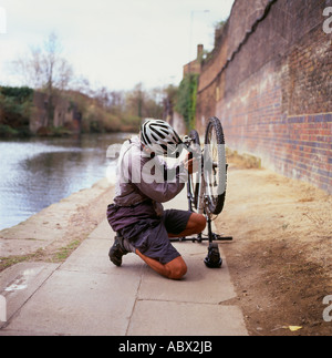 A cyclist  wearing a cycling helmet repairing his bicycle on Regents Canal path near Camden Lock London England - Stock Photo