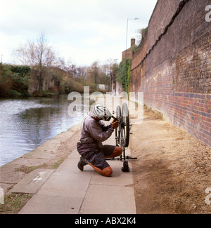 A cyclist  wearing a cycling helmet mending repairing his bicycle on the Regents Canal footpath near Camden Lock, - Stock Photo