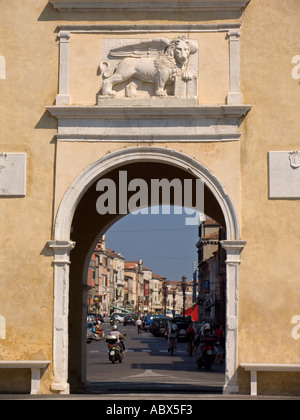 City entrance gate with Lion of St Mark frames main street of Chioggia Italy