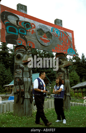 Totem poles and Tlingit Indians  in the Tlingit Indian village of Alaska AK - Stock Photo