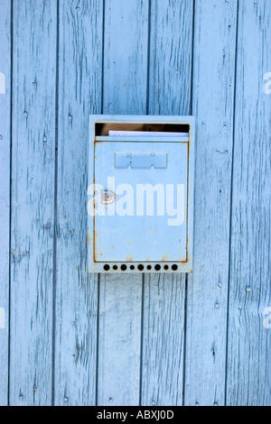 private home blue azur box letter on a old wooden door with letter inside in France street charente maritimes village - Stock Photo