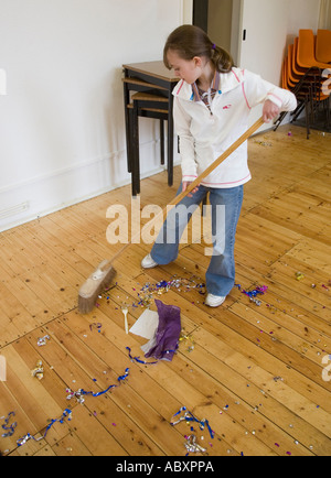Young girl helping to sweep up the day after a wedding party Wales UK - Stock Photo