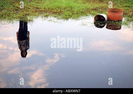 Young girl reflection in pond - Stock Photo