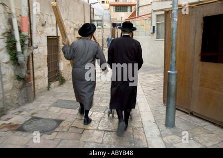 Israel Jerusalem Mea shearim Jewish Orthodox quarter 2 orthodox jews walking away in the courtyard of Beit Hahungarim - Stock Photo
