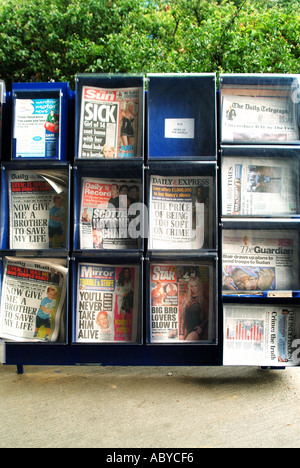 Selection of daily UK national newspapers in outdoor self service rack on forecourt of Tesco petrol filling station - Stock Photo