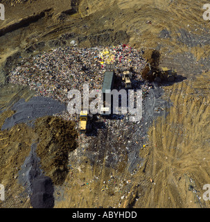 Trucks dumping refuse on landfill site low UK aerial view - Stock Photo