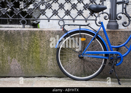 Blue bicycle stands against iron railings in Copenhagen, Denmark - Stock Photo
