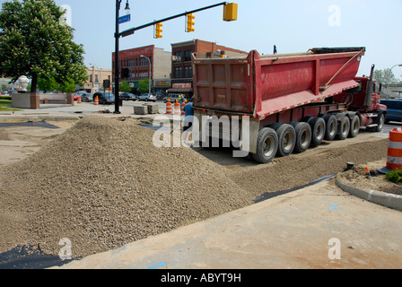 large industrial dump truck road making machinery and equipment is used to make a new paved street - Stock Photo