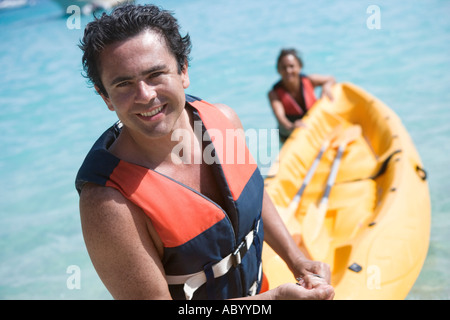 Couple pulling kayak out of water - Stock Photo