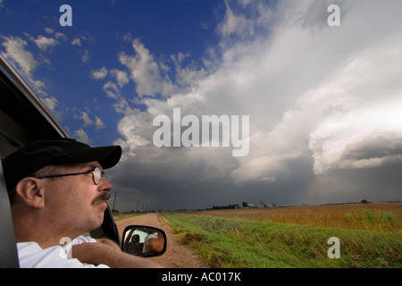 Storm chaser Darren Addy looks at severe storms in the distance from his car window near Minden, Nebraska. - Stock Photo