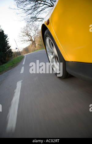 sports car going down a road - Stock Photo