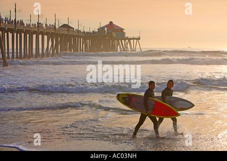 Surfers Walking Infront Of The Hunington Beach Pier Hunington Beach Orange County California United States MR - Stock Photo