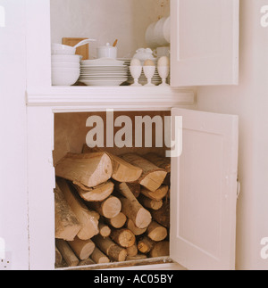 Open kitchen storage cupboards containing fire wood and crockery - Stock Photo