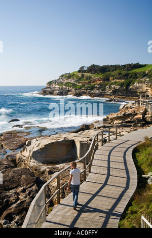 A walker on the Bondi to Coogee coastal walk along Sydney's rugged coastline and eastern beaches - Stock Photo