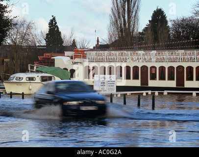 CAR MOVING through FLOODED STREET River Terrace in flood by River Thames  Henley on Thames Oxfordshire England - Stock Photo