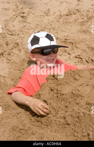 Wales Glamorgan Barry Island young boy buried in sand on the beach - Stock Photo