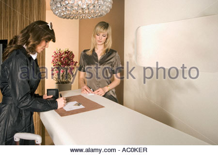 A woman standing at a checkout counter with a receptionist - Stock Photo