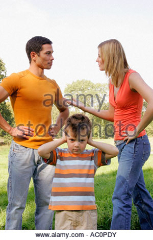 A young boy closes his ears as his parents argue - Stock Photo