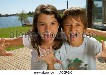 Boy and girl sticking their tongues out - Stock Photo