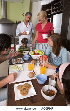 Parents telling their son to finish eating - Stock Photo