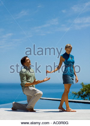 A man asking for forgiveness from his girlfriend - Stock Photo