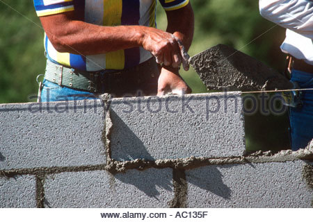 Block mason Bricklayer places concrete block taps with trowel to plumb line mortar oozes out - Stock Photo