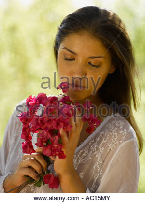 Close up of a young woman holding a bunch of flowers - Stock Photo
