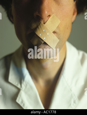 Mouth of a man taped with plaster - Stock Photo