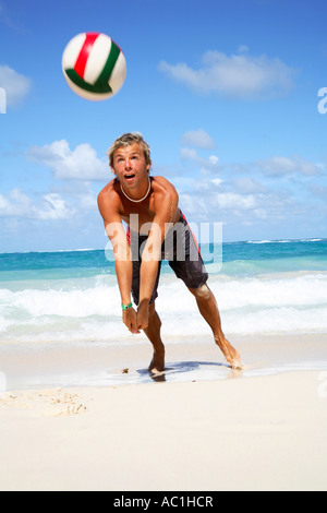 Young man playing volley ball on beach - Stock Photo