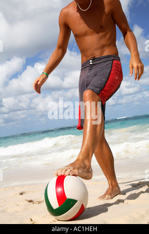 Young man playing football on beach - Stock Photo